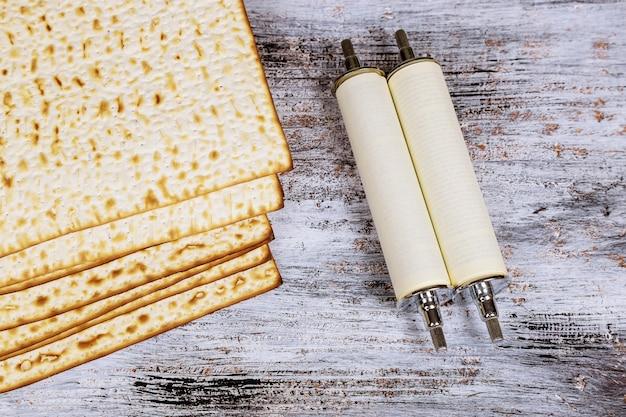 Draufsicht des passahfesthintergrundes. matzoh jüdisches feiertagsbrot und torahrolle während Premium Fotos