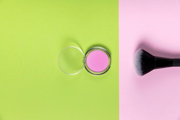 Draufsicht des pulvers und der bürste auf rosa und grünem hintergrund Kostenlose Fotos