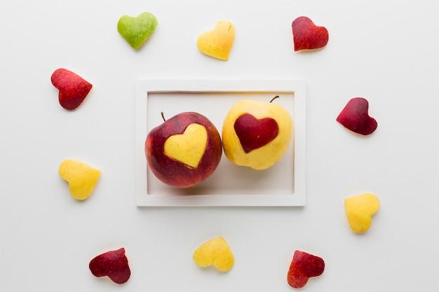 Draufsicht des rahmens mit äpfeln und fruchtherzformen Kostenlose Fotos