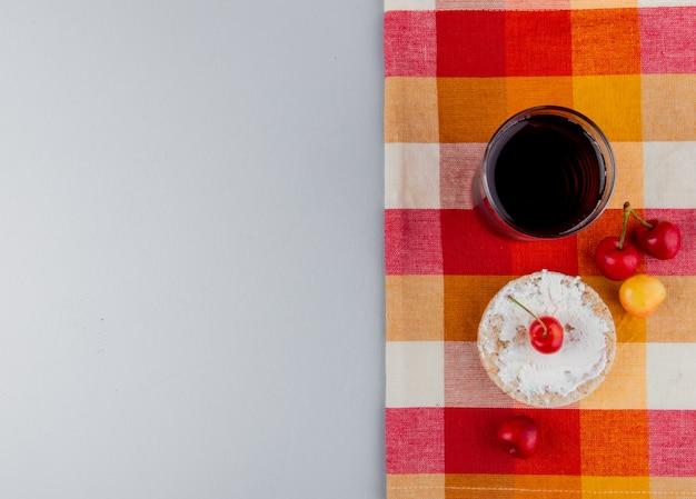 Draufsicht des reiskuchens mit frischkäse und frischen reifen regnerischen kirschen und einem glas kirschsaft auf karierter serviette auf grauem hintergrund mit kopienraum Kostenlose Fotos
