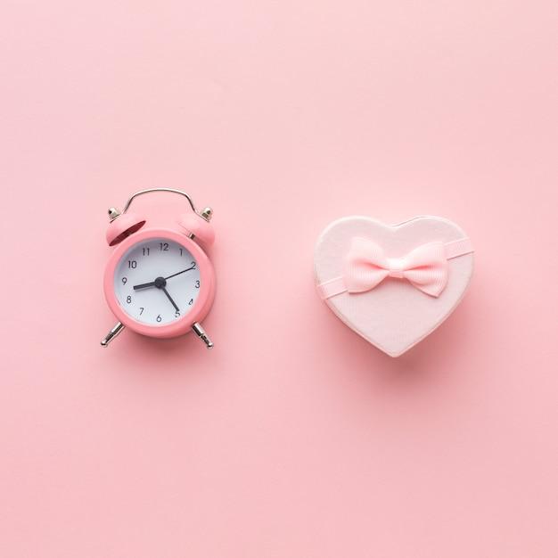 Draufsicht des rosa geschenks mit uhr Premium Fotos