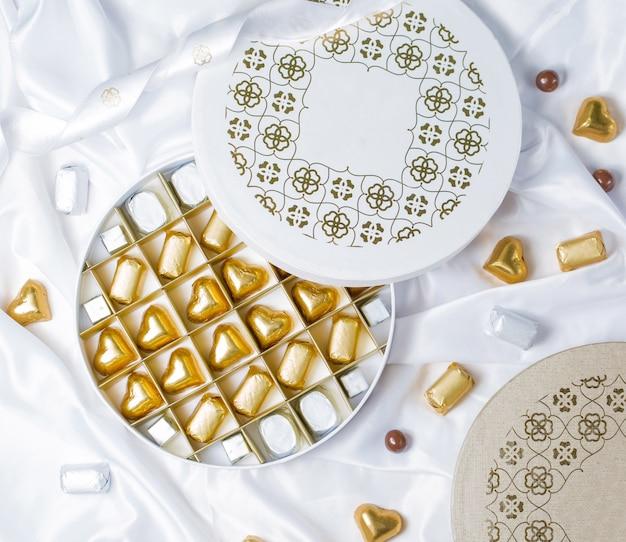 Draufsicht des runden schokoladenkastens mit den goldenen und silbernen eingewickelten schokoladen Kostenlose Fotos