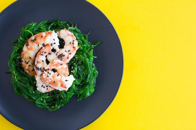 Draufsicht des salats mit seetang und roten garnelen in der schwarzen platte Premium Fotos