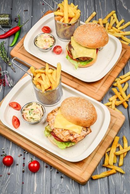 Draufsicht des schnellimbiss-tellers. fleischburger, kartoffelchips und keile. Premium Fotos