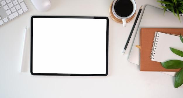 Draufsicht des schreibtischarbeitsplatzes für anwesendes werbungsprodukt auf tablettenschirm Premium Fotos