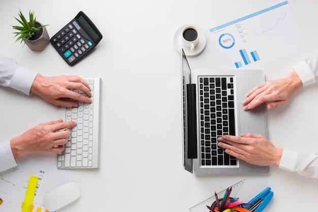 Draufsicht des schreibtisches mit den händen, die an laptop und tastatur arbeiten Kostenlose Fotos