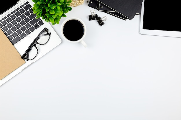 Draufsicht des schreibtischs mit arbeitsplatz im büro mit leerer notizbuchtablette und smartphone mit anderem büroartikel, mit kopienraum. Premium Fotos