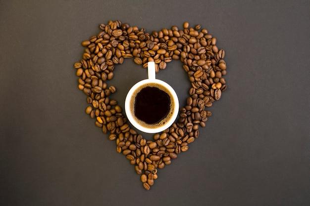 Draufsicht des schwarzen kaffees in der weißen tasse und im herzen gemacht von den kaffeebohnen auf dem dunklen hintergrund Premium Fotos
