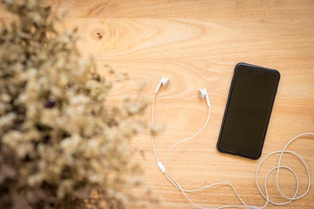 Draufsicht des schwarzen smartphone, kopfhörer auf rustikalem hölzernem hintergrund. Premium Fotos