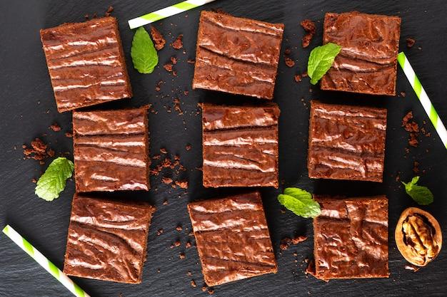 Draufsicht des selbst gemachten bäckereikonzeptes des lebensmittels von organischen schokoladenkuchen auf schwarzem schieferbrett Premium Fotos