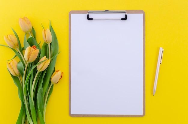 Draufsicht des sommerhintergrundes von gelben tulpen auf weißer tabelle mit klemmbrett und stift, kopienraum Premium Fotos
