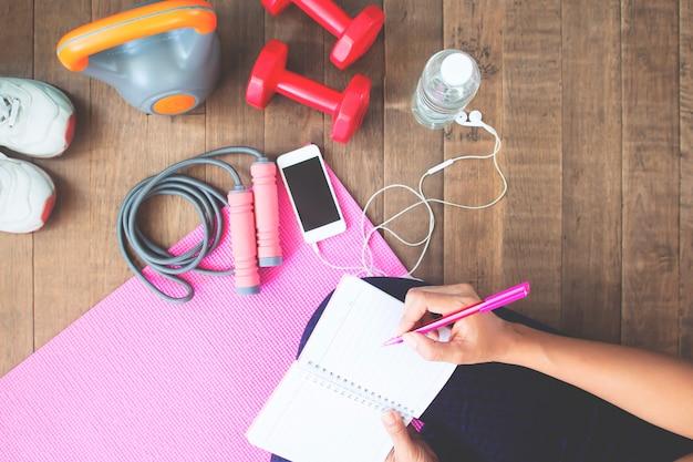 Draufsicht des sportlichen frauenschreibens auf notizbuch, planungstraining Premium Fotos