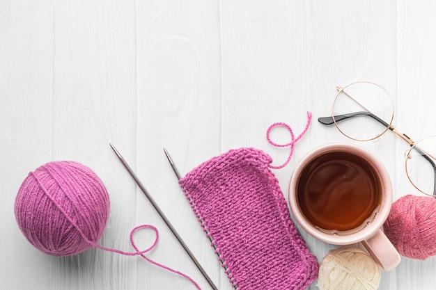 Draufsicht des stricksatzes mit garn und tee Premium Fotos