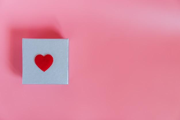 Draufsicht des süßen rosa hintergrundes mit einer silbernen geschenkbox und einer dekorationsdichtung Premium Fotos