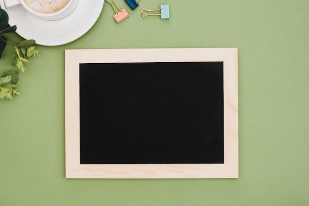 Draufsicht des tafelrahmens mit kaffeetasse, über grünem hintergrund. mock up für design. kopieren sie platz. Premium Fotos