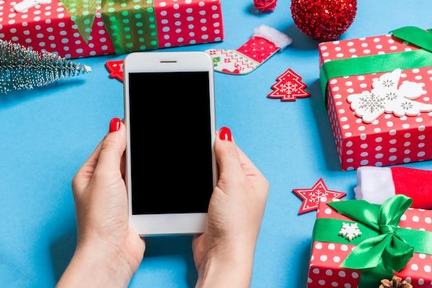 Draufsicht des telefons in der weiblichen hand auf festlichem blau Premium Fotos