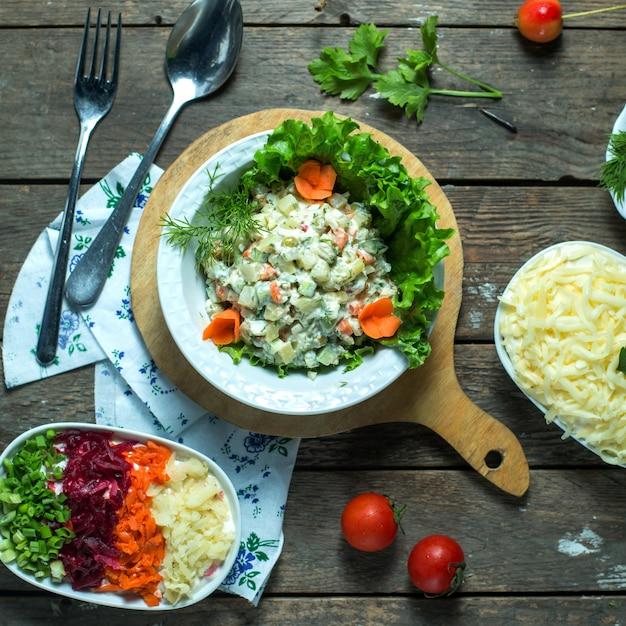 Draufsicht des traditionellen russischen oliviersalats mit hühnergrüner erbse und gemüse in einem weißen teller auf einem holzbrett Kostenlose Fotos