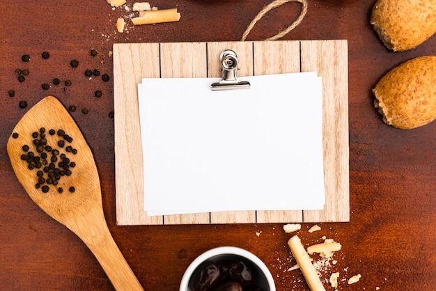 Draufsicht des unbelegten weißbuches mit klemmbrett; brötchen; brotstangen; pfefferkorn mit spachtel auf schreibtisch aus holz Kostenlose Fotos