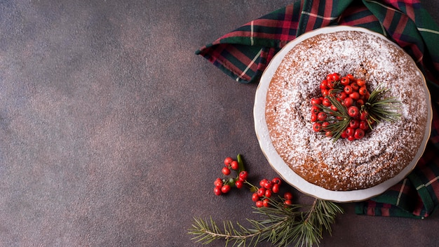 Draufsicht des weihnachtskuchens mit kopienraum und roten beeren Kostenlose Fotos