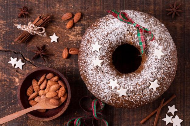 Draufsicht des weihnachtskuchens mit mandeln und zimtstangen Kostenlose Fotos