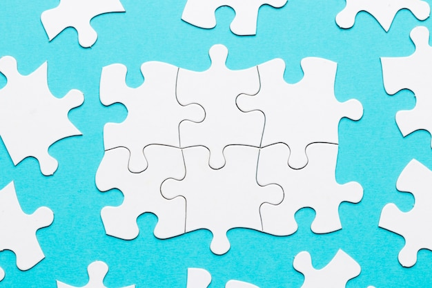 Draufsicht des weißen puzzlestücks auf blauem hintergrund Kostenlose Fotos