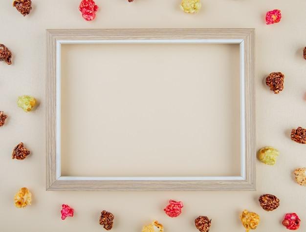 Draufsicht des weißen rahmens mit kegelpopcorn herum auf weißer oberfläche mit kopienraum Kostenlose Fotos