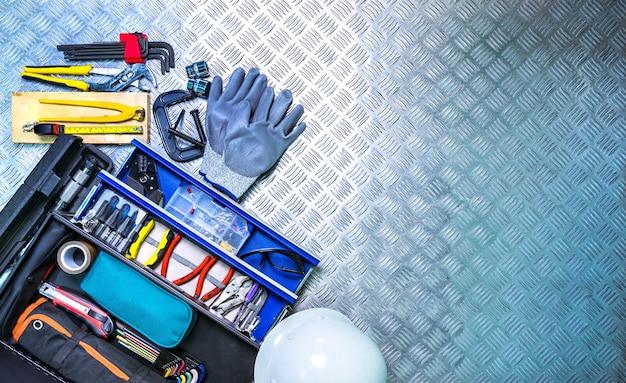 Draufsicht des werkzeugkastens und -sturzhelms auf kariertem plattenhintergrund in der werkstatt Premium Fotos