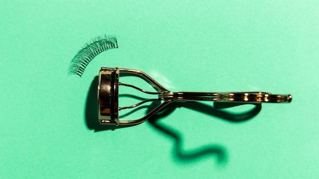 Draufsicht des wimperlockenwicklers auf einfachem hintergrund Kostenlose Fotos