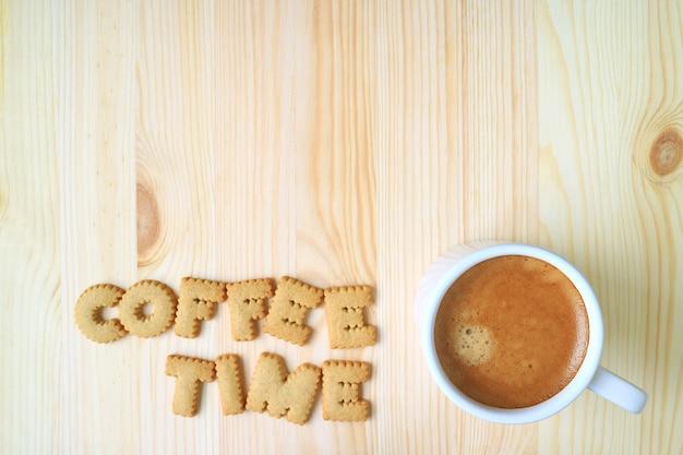 Draufsicht des wortes kaffeezeit, die mit alphabetkeksen und einem tasse kaffee auf holztisch buchstabiert Premium Fotos