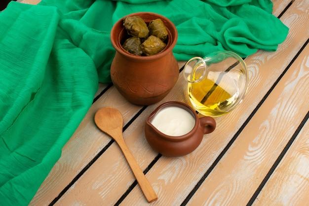 Draufsicht dolma im braunen topf zusammen mit olivenöl und joghurt auf dem rustikalen holzboden Kostenlose Fotos