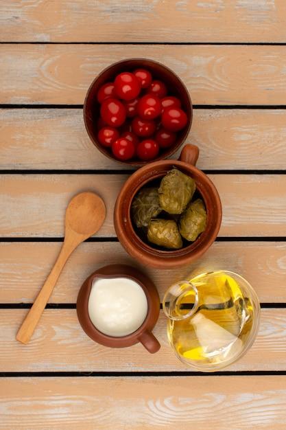 Draufsicht dolma mit joghurt-olivenöl und tomaten auf dem holz Kostenlose Fotos