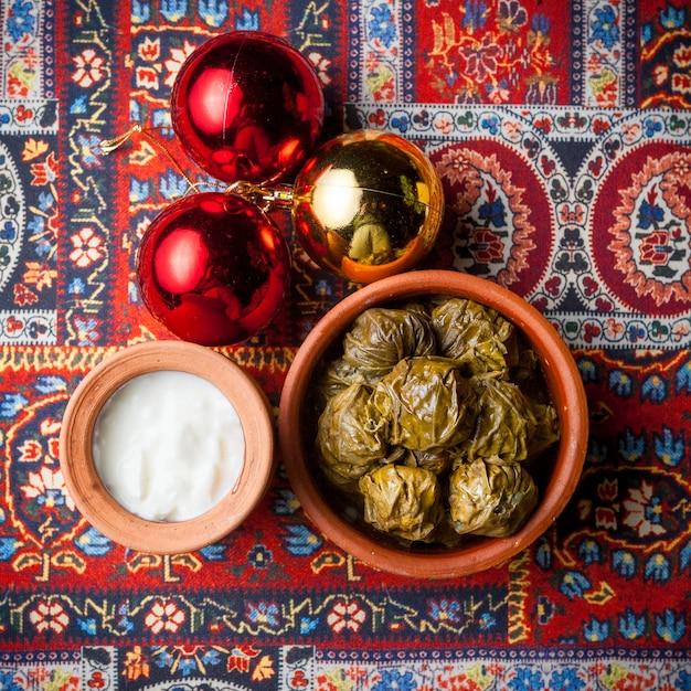 Draufsicht dolma mit joghurt und weihnachtskugeln in einer tonplatte auf teppich Kostenlose Fotos