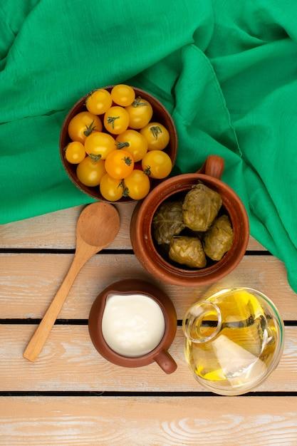 Draufsicht dolma mit joghurt zusammen mit gelben tomaten und olivenöl auf dem grünen taschentuch und dem rustikalen holzboden Kostenlose Fotos