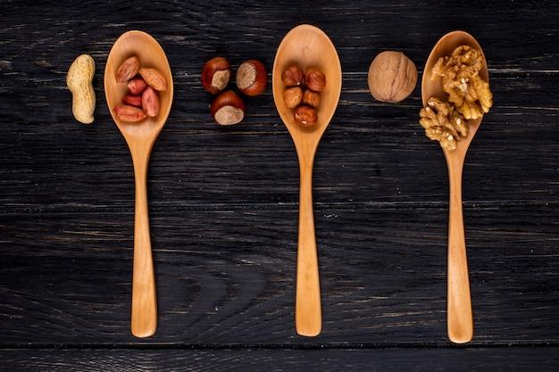 Draufsicht drei holzlöffel mit haselnüssen, erdnüssen und walnüssen geschält und in der schale Kostenlose Fotos