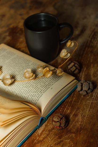 Draufsicht ein altes buch mit kaffeetasse und getrockneten blumen auf holztisch. vertikale Kostenlose Fotos