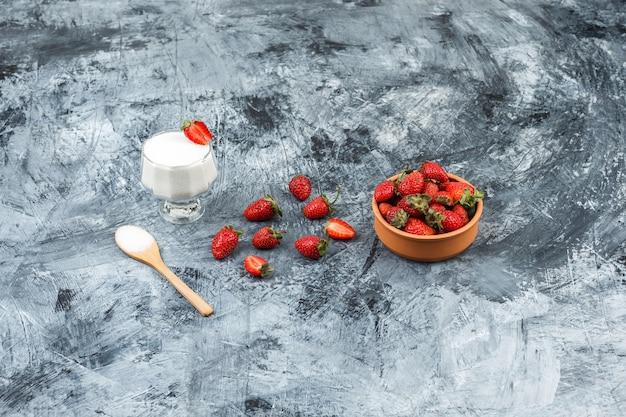 Draufsicht eine glasschale joghurt auf weiden-tischset mit holzlöffel und erdbeeren auf dunkelblauem marmor und weißer holzbrettoberfläche. vertikal Kostenlose Fotos