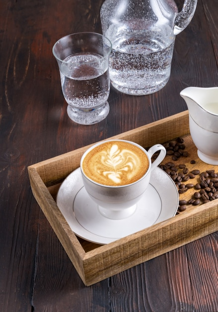 Draufsicht eine tasse latte art kaffee, wasser und kaffeebohnen in einer holzkiste auf einer dunkelheit Premium Fotos