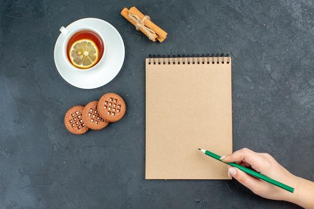 Draufsicht eine tasse tee mit zitronen-zimtstangen-keksen grüner bleistift in weiblicher hand auf dunkler oberfläche Kostenlose Fotos