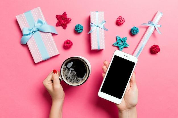 Draufsicht einer frau, die ein telefon in einer hand und einen tasse kaffee in einer anderen hand auf rosa hintergrund hält. weihnachtsdekoration und spielzeug. neujahrsfeiertagskonzept. attrappe, lehrmodell, simulation Premium Fotos