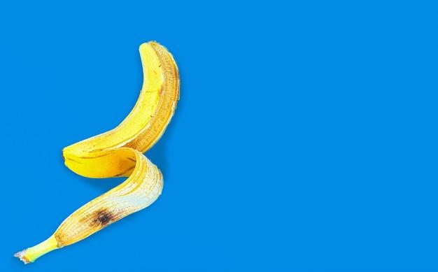 Draufsicht einer gelben bananenschale, die auf einer blauen oberfläche liegt Kostenlose Fotos