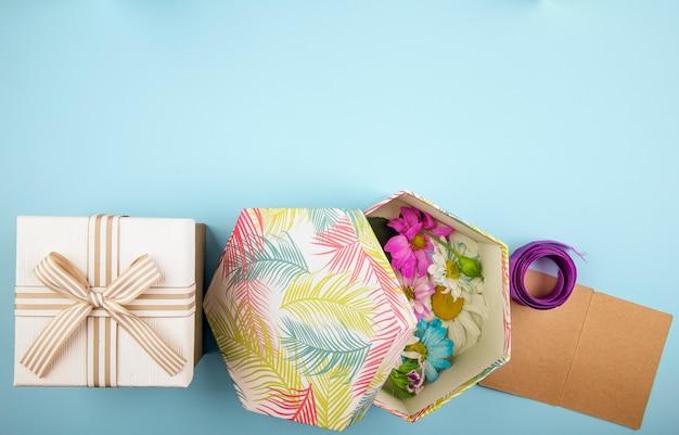 Draufsicht einer geschenkbox gebunden mit schleife und einer geschenkbox gefüllt mit bunten chrysanthemenblumen mit gänseblümchen und lila band mit kleiner postkarte auf blauem hintergrund Kostenlose Fotos