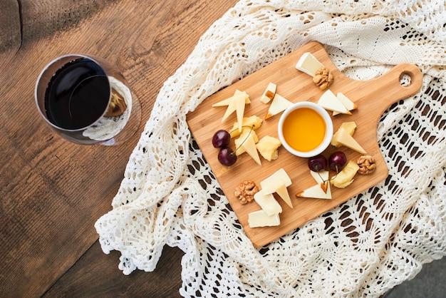 Draufsicht einer käsemischung aus parmesan, mozzarella, camembert auf einem holzbrett und einem glas rotwein Premium Fotos