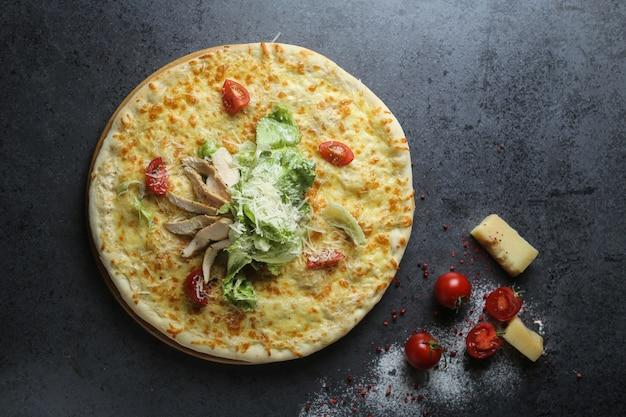 Draufsicht einer köstlichen pizza mit tomaten und käse auf einem tisch Kostenlose Fotos