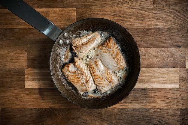 Draufsicht einer pfanne mit gebratenem fleisch auf einem holztisch Kostenlose Fotos