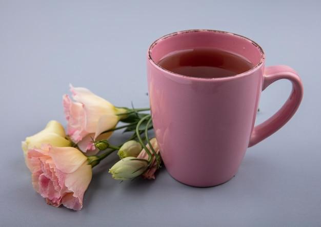 Draufsicht einer rosa tasse tee mit frischen blumen auf einem grauen hintergrund Kostenlose Fotos