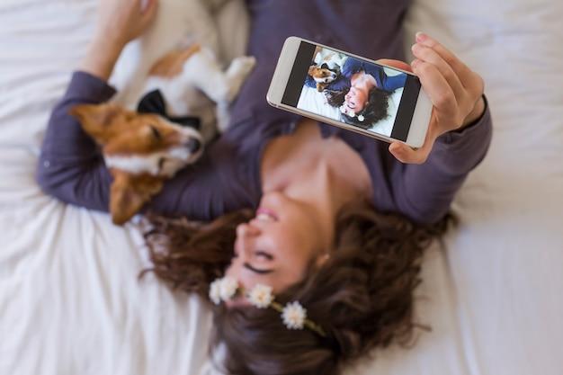 Draufsicht einer schönen jungen frau, die außerdem ein selfie mit handy auf bett mit ihrem netten kleinen hund nimmt. zuhause, drinnen und lifestyle Premium Fotos