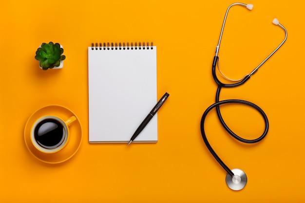 Draufsicht einer tabelle eines doktors mit notizblock- und stiftstethoskop, tastatur, verordnung und pillen, ein tasse kaffee auf einem gelben hintergrund Premium Fotos
