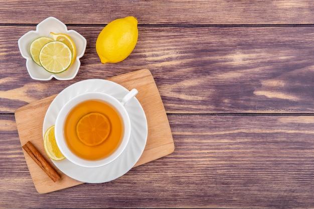 Draufsicht einer tasse schwarzen tees mit zitronen-zimtstange auf hölzernem küchenbrett mit zitronenscheiben auf weißer schüssel auf holz Kostenlose Fotos