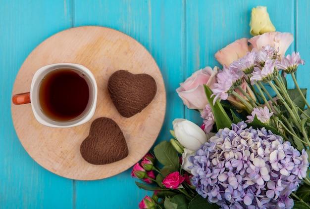 Draufsicht einer tasse tee auf einem hölzernen küchenbrett mit herzformplätzchen mit wunderbaren frischen blumen lokalisiert auf einem blauen hölzernen hintergrund Kostenlose Fotos