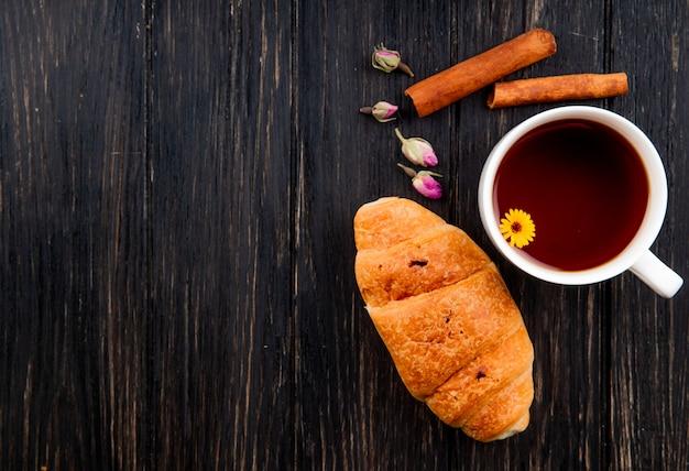 Draufsicht einer tasse tee mit croissant und zimtstangen auf schwarzem holz mit kopierraum Kostenlose Fotos